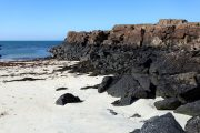 Black rocks on the sandy beach of Port Na Ba, Isle of Mull, Inner Hebrides of Scotland
