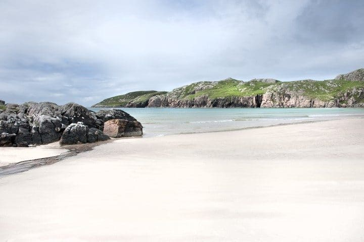 Scotland: White beach of Scourie bay with green grass and rocky cliffs